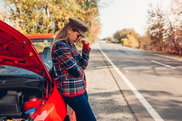 Coche roto triste mujer de pie en la carretera junto a su auto con capó abierto esperando ayuda