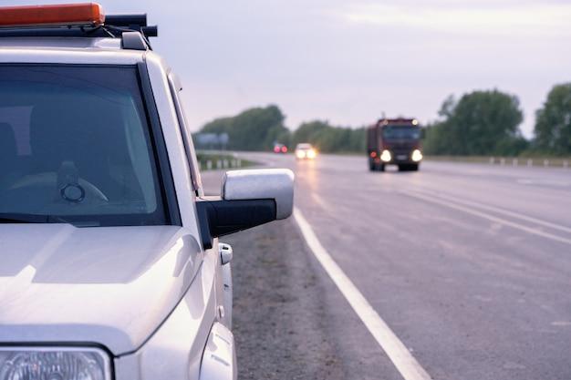 Un coche de seguridad con una luz intermitente está en la carretera.