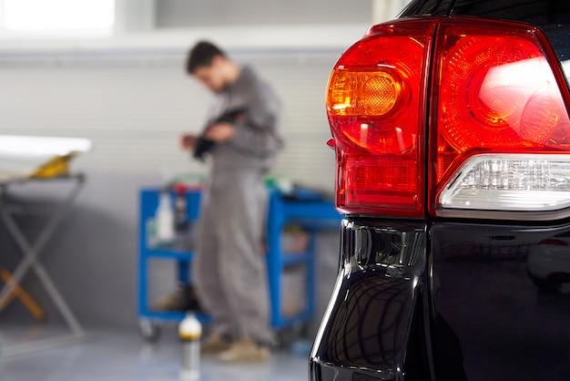 Coche en taller de reparación de automóviles con mecánico sobre un fondo