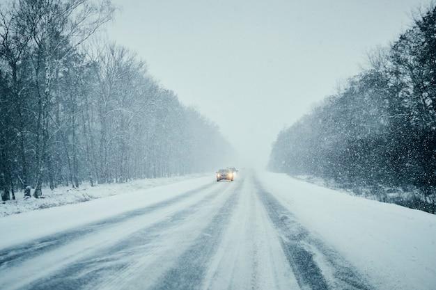 Coche en tormenta en carretera de invierno con tráfico. peligro al conducir en invierno. vista en primera persona
