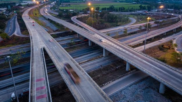 Coche de tráfico del movimiento de la exposición larga del paisaje crepuscular en el intercambio de la autopista en tailandia
