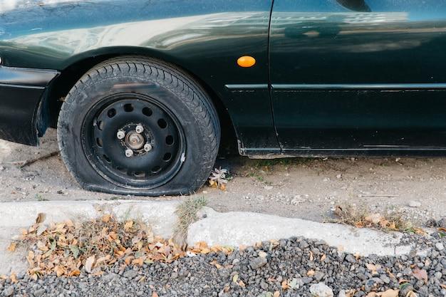 Coche verde con una rueda pinchada al aire libre. llanta pinchada dañada de un automóvil.