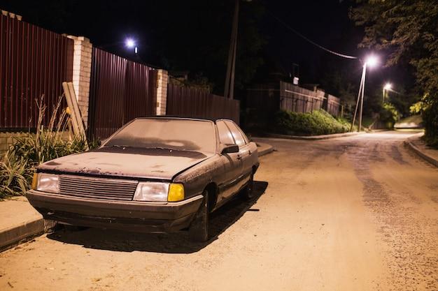 Coche viejo en el polvo de pie en la carretera. antigua carretera vacía. camino en la noche. linterna ilumina una calle oscura