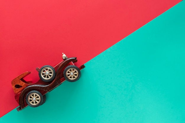 Coche vintage retro sobre fondo de papel multicolor. vacaciones, entrega, concepto de viaje. vista superior, endecha plana. estípites de menta roja.
