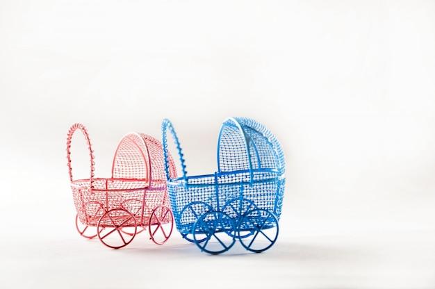 Cochecitos de niño miniatura en un primer plano de fondo blanco. concepto de bebé y embarazo y copia espacio.