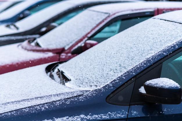 Coches cubiertos de nieve en el aparcamiento.