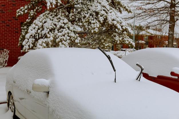 Coches cubiertos de nieve en la ventisca de invierno