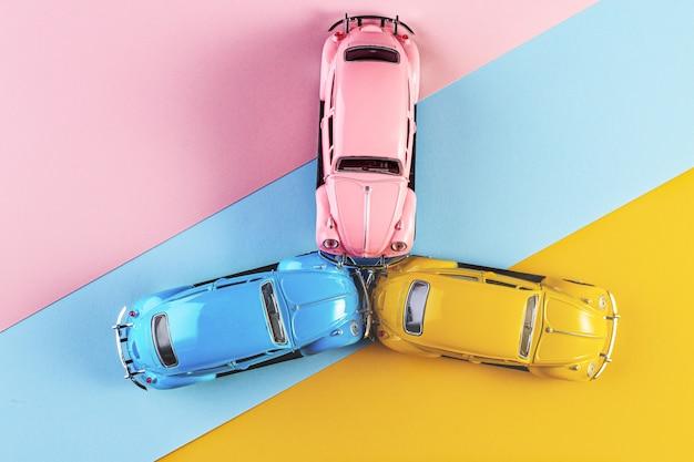 Coches de juguete en accidente sobre un fondo colorido pastel. carreras de coches en la pista de carreras.