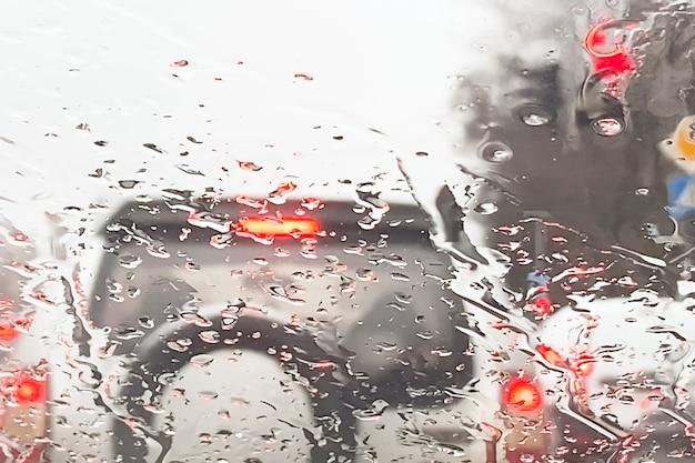 Coches ligeros, semáforo a través de la ventana con gotas de lluvia
