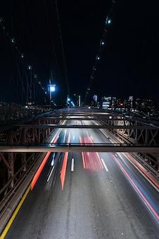Coches en puente con movimiento borroso en la noche