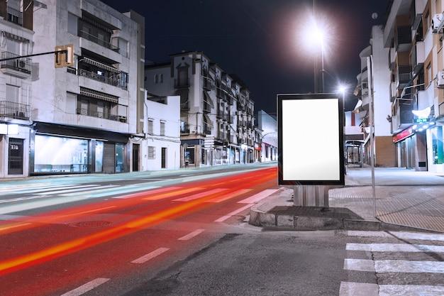 Coches senderos de luz que pasan cerca de la cartelera en blanco en la acera de la ciudad