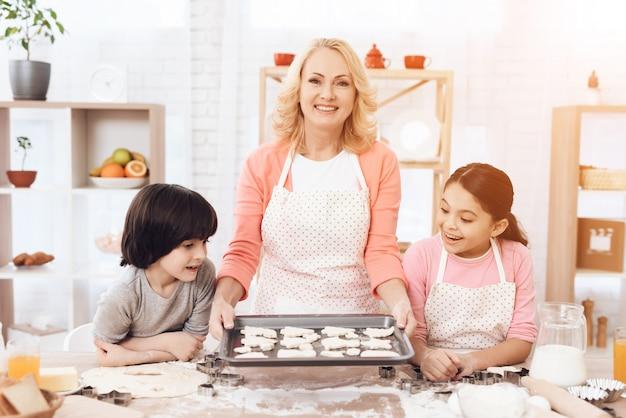 Cocina de la abuela que hornea las galletas con los nietos