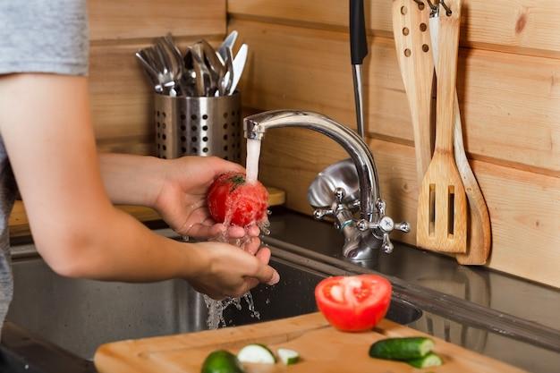 En la cocina con agua corriente las manos de las mujeres lavan tomates maduros