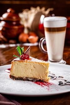 Cocina americana, europea. tarta de queso con chocolate y cereza encima. postre vegano y café con leche en el restaurante.