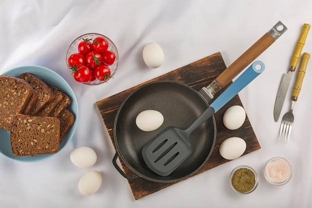 Cocina casera. huevos, tomates cherry hierbas pan