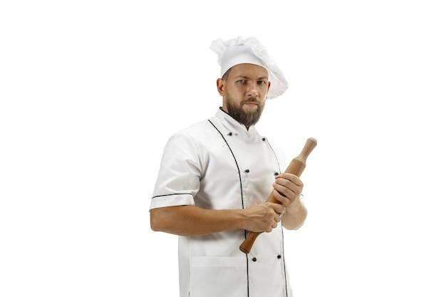 Cocina, chef, panadero en uniforme aislado sobre fondo blanco de estudio, gourmet. hombre joven, retrato de cocinero de restaurante. negocio, piso, ocupación profesional, concepto de emociones. copyspace para anuncio.