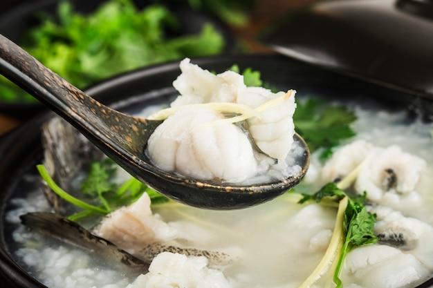 Cocina china congee con rodajas de pescado en cazuela