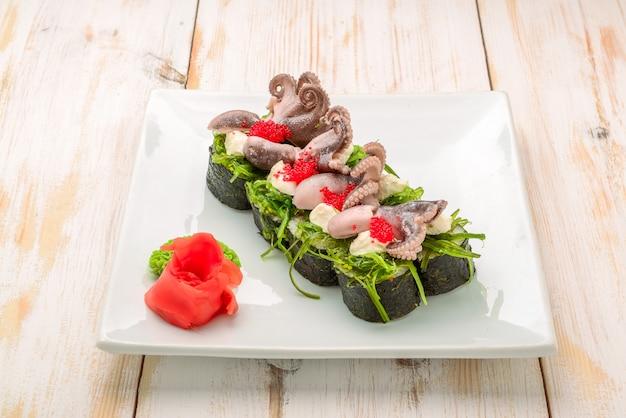 Cocina, cocina asiática, concepto de venta y comida: cerca de las manos con pinzas para tomar sushi en el mercado callejero surtido de sushi fresco
