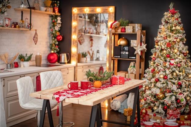 Cocina decorada con guirnaldas de pino y juguetes navideños. vale la mesa y cerca del árbol de navidad. cocina interior luminosa decorada para feliz navidad y felices fiestas!