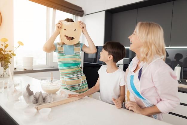 Cocina familiar feliz. mujer crear cara fuera de la masa.