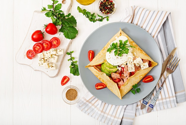 Cocina francés. desayuno, almuerzo, meriendas. panqueques con huevo escalfado, queso feta, jamón frito, aguacate y tomates en mesa blanca. vista superior