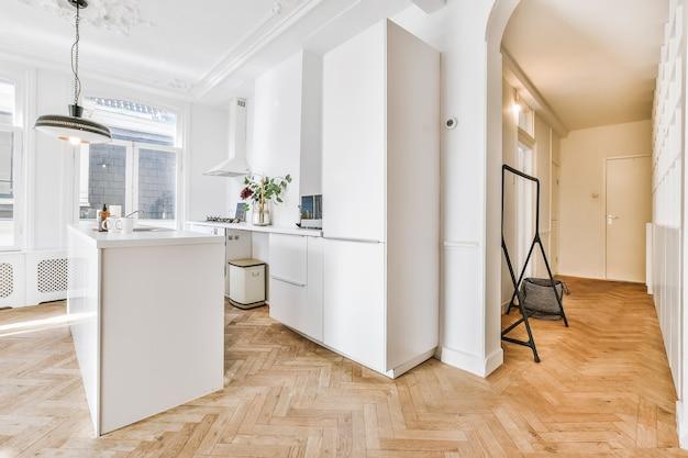Cocina de galera moderna con gabinetes de madera y diseño minimalista en ático estudio con paredes blancas