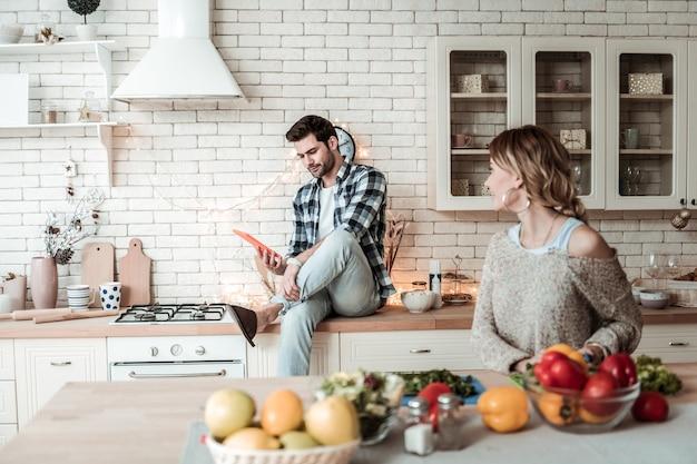 En la cocina. hombre atractivo joven de pelo oscuro con una camisa a cuadros y su esposa pasar tiempo juntos en la cocina