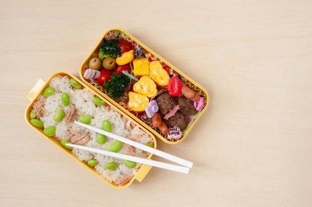 Cocina japonesa: caja bento casera tradicional con arroz, carne, huevo, pescado, verduras y cereales.
