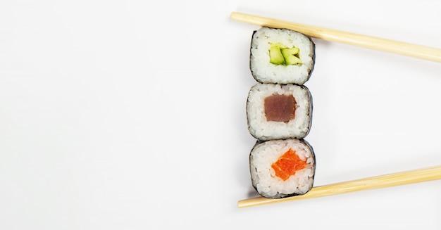 Cocina japonesa varios sushi y rollos con queso de pescado y ensalada de chuka en palillos