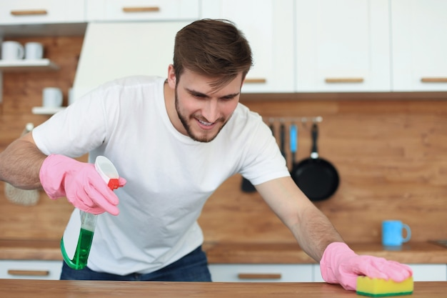 Cocina de limpieza de hombre guapo solo en casa.