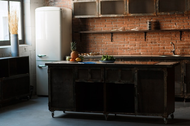 Cocina de loft oscuro con pared de ladrillo rojo. mesa de cocina cubiertos, cucharas, tenedores, fruta de desayuno.