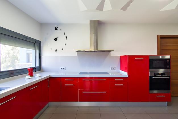 Cocina moderna en rojo, con vista exterior. diseño interior de casa.