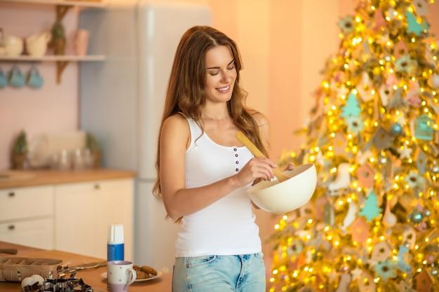 En la cocina. mujer bonita en camiseta blanca revolviendo algo en un recipiente y sonriendo