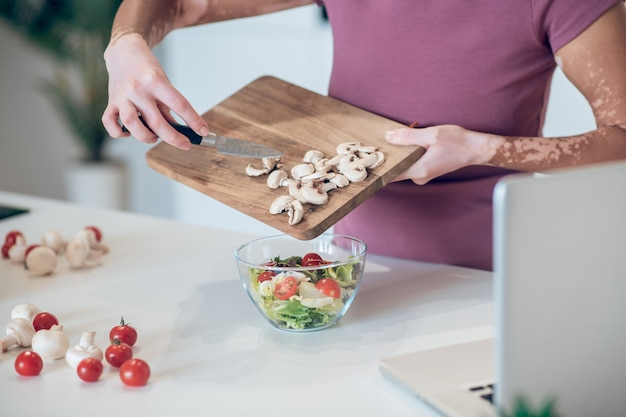 En la cocina. una mujer de piel oscura cortando verduras y luciendo involucrada