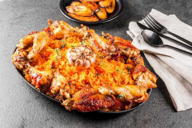 Cocina nacional de áfrica occidental. arroz jollof con alitas de pollo a la parrilla y plátanos fritos
