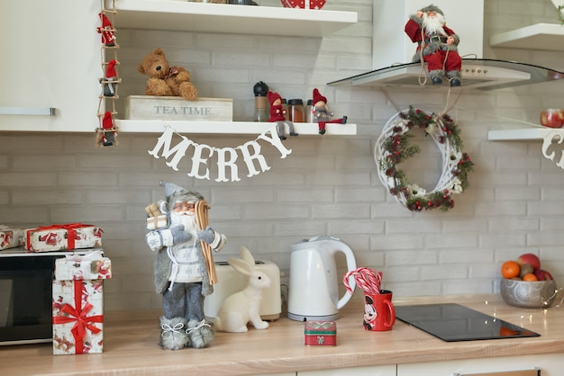 Cocina navideña en estilo loft, utensilios de cocina. cocina interior luminosa con decoración navideña y árbol. diseño moderno de cocina, muebles de cocina blancos. humor navideño.