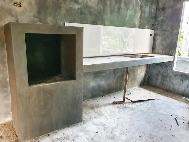 La cocina de la nueva casa en construcción tiene una encimera de cerámica blanca y un compartimento para horno.