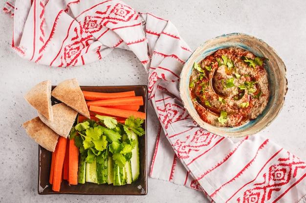 Cocina de oriente medio: baba ganoush en un plato sobre fondo blanco.