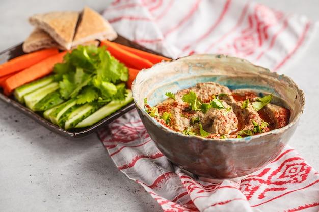 Cocina de oriente medio: baba ganoush con verduras en un plato sobre fondo blanco.