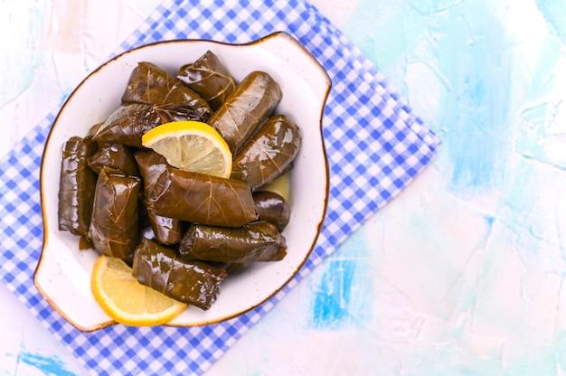 Cocina tradicional griega. arroz envuelto en hojas de parra. dolma con limón y especias. comida casera ramas de olivo y varios aperitivos picantes