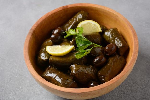 Cocina tradicional griega. arroz envuelto en hojas de parra. dolma con limón, especias, diversas aceitunas en escabeche y pimientos picantes.