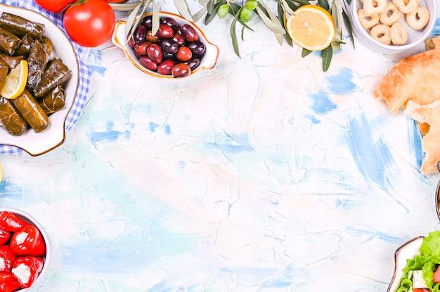 Cocina tradicional griega. arroz envuelto en hojas de parra. dolma con limón, especias, varias aceitunas en escabeche y pimientos picantes. ramas frescas y comida casera.