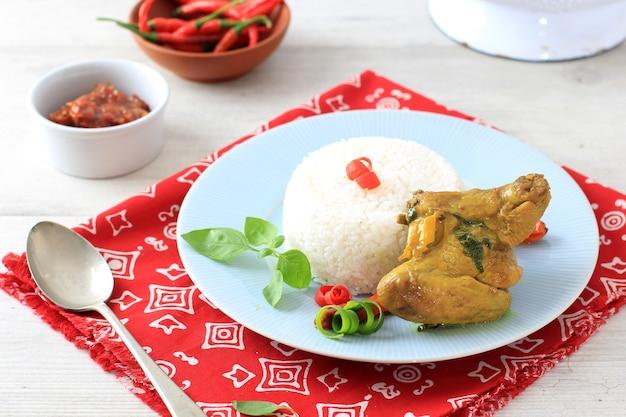 Cocina tradicional indonesia: ayam woku, o pollo condimentado con cúrcuma y albahaca dulce asiática, un plato de pollo manadonés servido con arroz