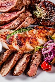 Cocina turca. surtido de diferentes carnes a la parrilla, cordero, pollo, cerdo con verduras a la parrilla. sirviendo platos en un restaurante en una placa blanca.