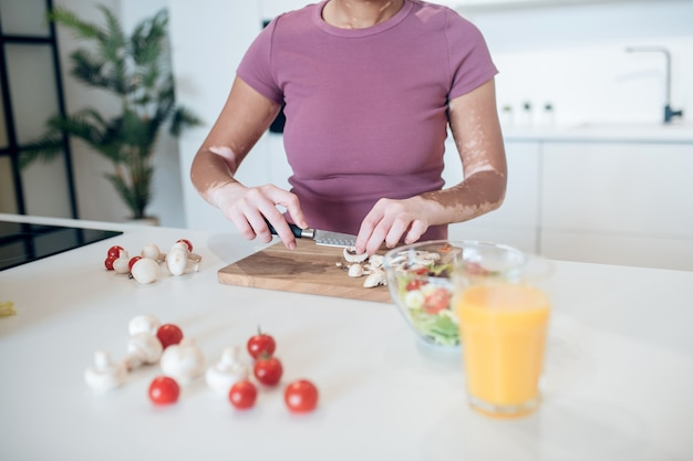 Cocinando. una mujer de piel oscura cocinando en la cocina y cortando verduras