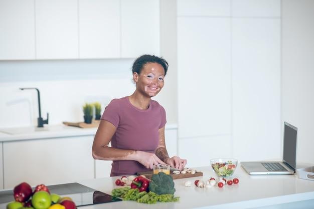 Cocinando. una mujer de piel oscura cocinando en la cocina mientras ve un vlog de cocina