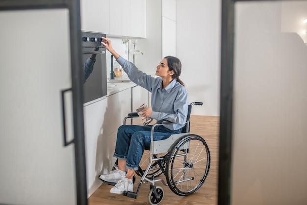 Cocinando. una niña en una silla de ruedas abriendo el horno en la cocina mientras cocina algo