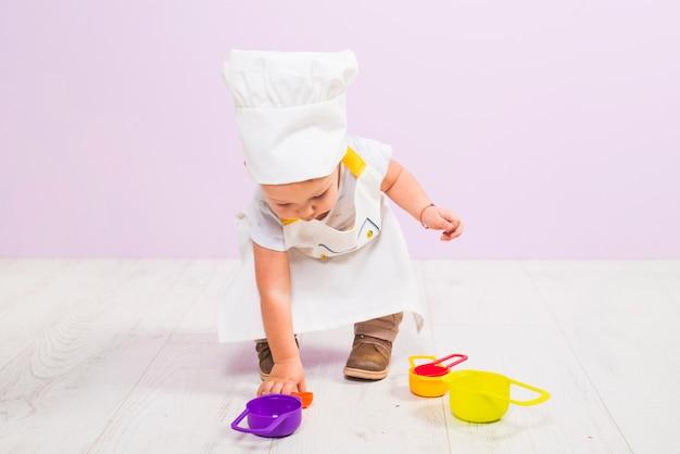 Cocinar al niño jugando con platos de juguete.