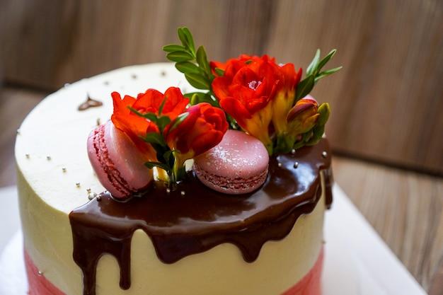 Cocinar bizcocho decorado con flores frescas y galletas