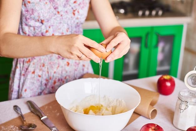 Cocinar en casa. romper un huevo en una harina. primer plano de manos de mujer rompe un huevo para pastelería